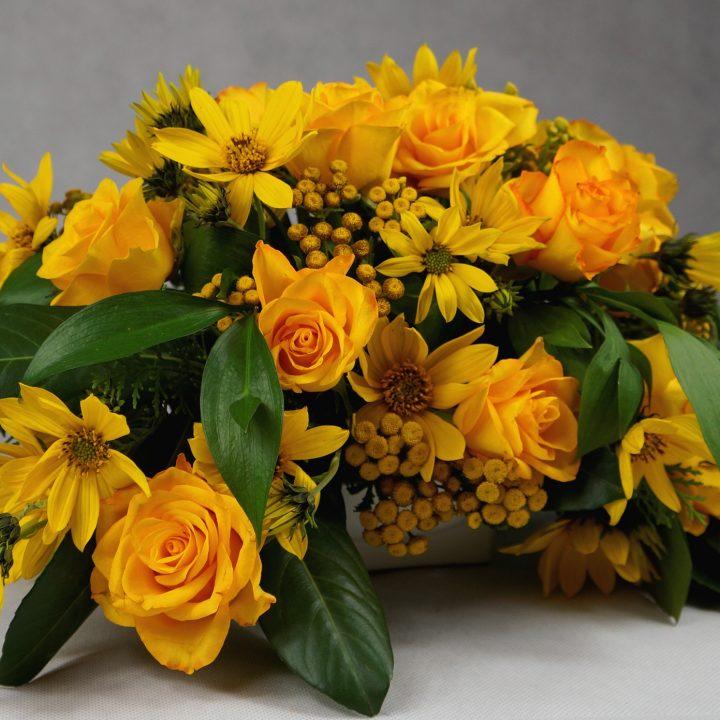 украса на маса с жълти рози и сезонна зеленина